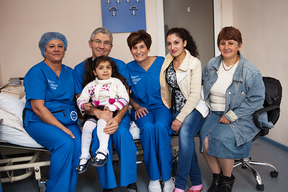Oral and maxillofacial surgeon Dr. Armond Kotikian with a cleft palate patient prior to surgery, joined by Juliet Khodadadi, Rebecca Berberian and family members