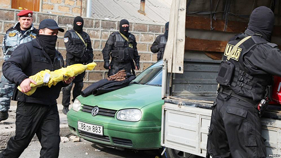 Armenia's National Security Service officers empty arms after a raid on a house in suburban Yerevan Wednesday