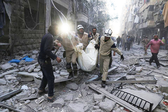 Syrian emergency personnel carry a body following an air strike on Nov. 3,, in the rebel-held side of the northern city of Aleppo (Photo by Baraa Al-Halabi) for AFP)