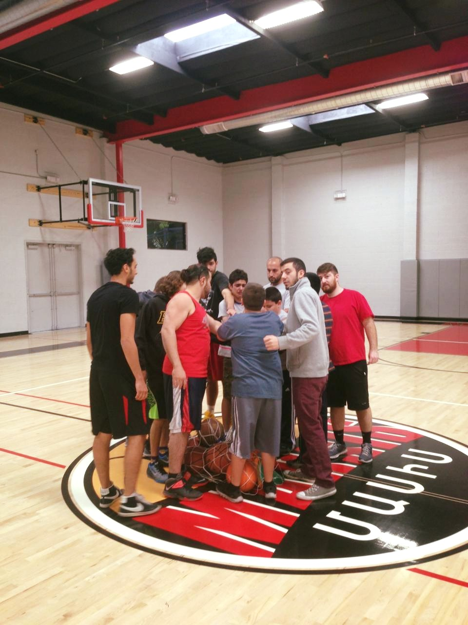AYF members and volunteers huddle with players during practice