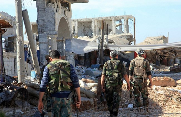 Pro-government fighters walk past debris in the Syrian town of Arbid on the outskirts of Kweyris military airbase, in the northern Syrian province of Aleppo, on November 12, 2015 (Source: AFP PHOTO / George Ourfalian)