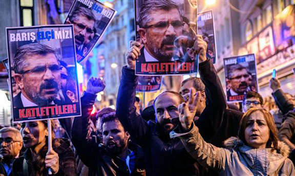 """Protesters hold pictures of lawyer Tahir Elci reading """"They slaughtered him!"""" during a demostration on Istiklal avenue in Istanbul after he was killed in Diyarbakır on November 28, 2015 (Source: AFP Photo)"""