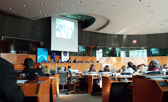 The audience views a video presentation during the hearing