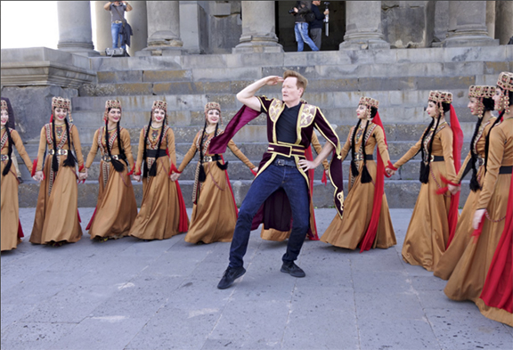 Conan attempts a traditional Armenian dance in front of the Garni Temple (Photo by Aaron Bleyaert