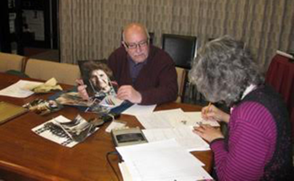 """March 1, 2011, with tape recorder running, and Suzanne Adams, Archivist, taking the photo, Tom shares a photo he took of his mother, Ojen """"Jennie"""" Hekimian Vartabedian, and shares her accomplishments as a Genocide Survivor with Ruth."""