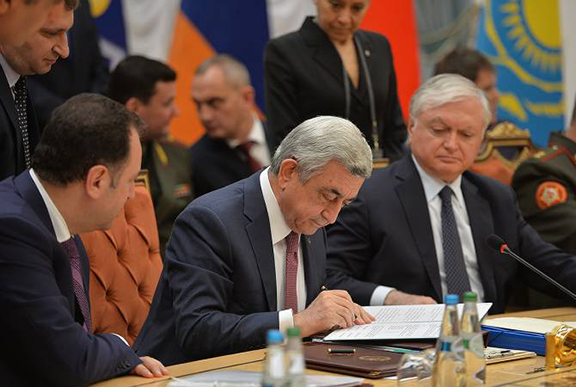 President Serzh Sarkisian signs a document as Armenia;s Foreign Minister Edward Nalbandian (right) and Defense Minister Vigen Sargsyan look on