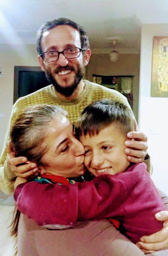 Nurcan Vayiç Aksu (left) and Cemil Aksu (standing) with their son, Arev upon being released from prison