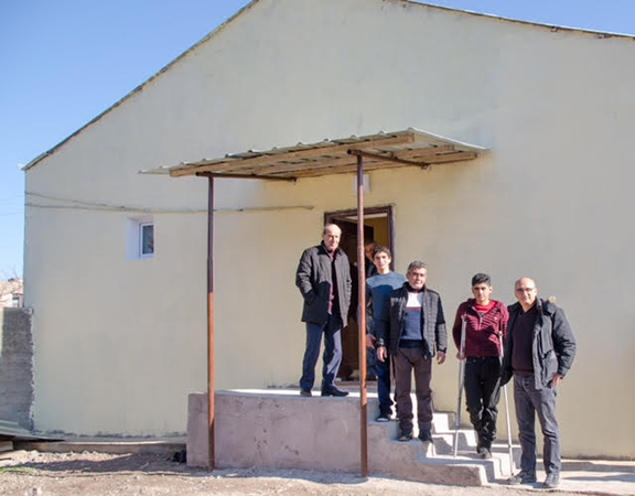 The Askarian family in front of their new home in Kashatagh