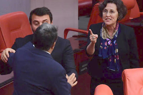 HDP's Filiz Kerestecioglu (R) confronts AKP's Bayram Ozcelik (L) as another lawmaker holds the former during a scuffle at the Turkish Parliament, Ankara, March 7, 2018. (Photo: DHA)