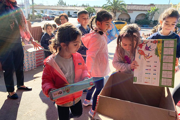 Tufenkian Preschool students handing in toys for the Spark of Love toy drive