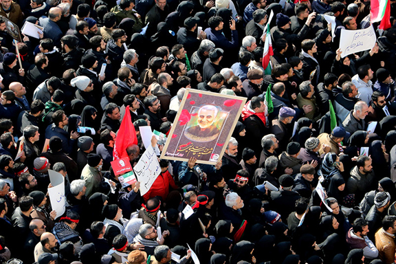 Iranian mourners lift a picture of slain military commander Qasem Soleimani during a funeral procession in the capital Tehran on January 6, 2020, (AFP Photo by ATTA KENARE)