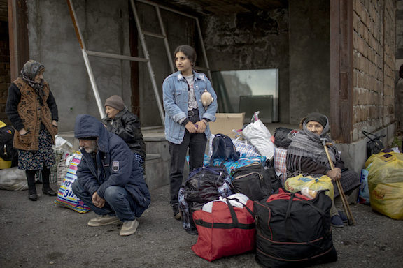People wait to take a bus to return to Stepanakert, in Yerevan, Armenia, on November 19, 2020. (Photo by Anush Babajanyan for POLITICO).