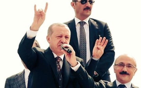 Turkish President Recep Tayyip Erdogan salutes a crowd with the ultranationalist Grey Wolves sign at a gathering of his supporters in 2018